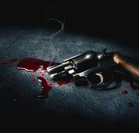 crime scene concept with a gun on a blood puddle, high contrast image Stock Photo