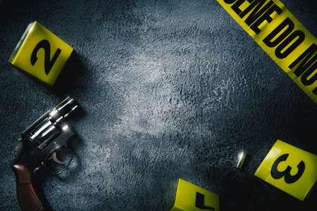 Crime scene concept with a gun and evidence markers , high contrast image Stockfoto