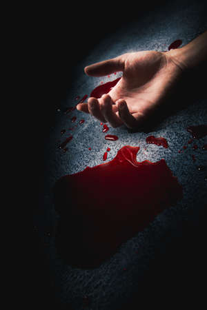 hand on a puddle of blood with dramatic lighting