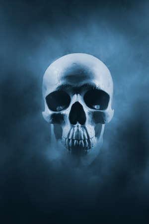 Gruseliger Schädel, der aus einer Rauchwolke auftaucht / kontrastreiches Bild Standard-Bild