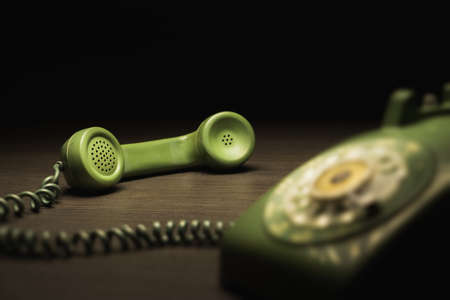 High contrast image of old rotary telephone on a wooden surface /selective focus