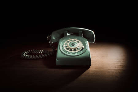 High contrast image of a vintage telephone with rotary dial on a wooden background Stockfoto