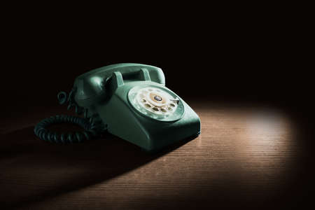 High contrast image of a vintage telephone with rotary dial on a wooden background Stock Photo