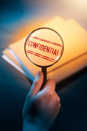 Private investigator holding a magnifying glass focusing on confidential envelopes Stock Photo