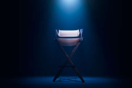 Back of a vintage director chair on a smokey background  high contrast image Stock Photo