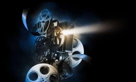 Fondo de cine con proyector de películas y rollos de película sobre un fondo oscuro / imagen de alto contraste Foto de archivo