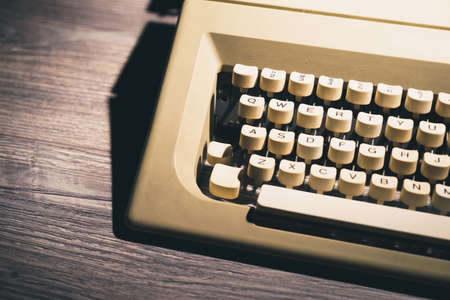 High contrast image of a retro typewriter on a wooden background