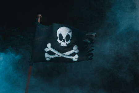 Pirate flag waving with the wind on a smoky background Stockfoto
