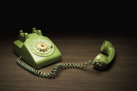 High contrast image of old rotary telephone on a wooden surface Stock Photo