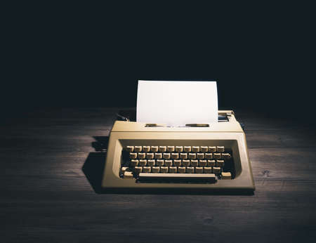 High contrast image of a retro typewriter with a blank sheet of paper on a wooden background