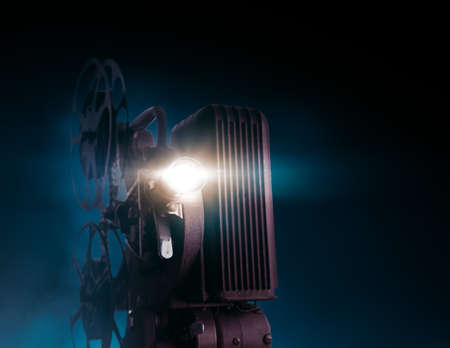 Movie projector on a dark background with light beam  high contrast image