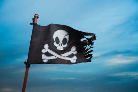 Pirate flag waving with the wind at sea