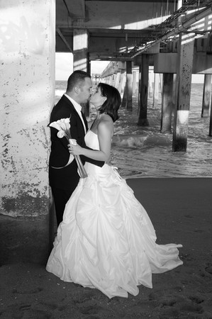 Newlyweds Kissing Under the Pier Imagens