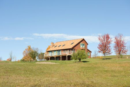 Beautiful Log Cabin House surrounded by trees changing colors in fall