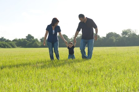 Family of Three Walking in a field