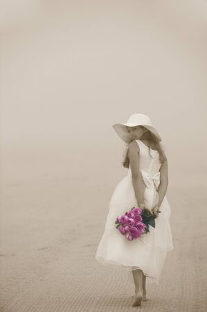 Beautiful young girl walking at the beach with a bouquet of roses