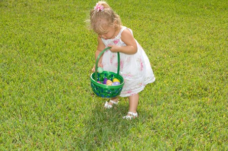 Adorable little girl collecting Easter eggs in her basket Stok Fotoğraf