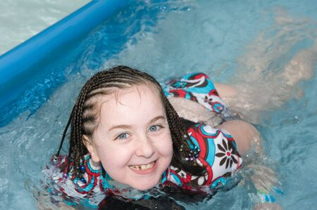 Adorable young girl laying in swimming pool Stock Photo