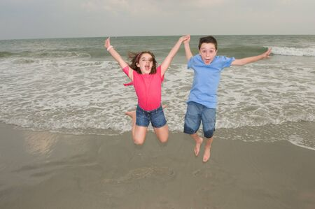 Happy Kids Jumping for Joy at the beach Stockfoto
