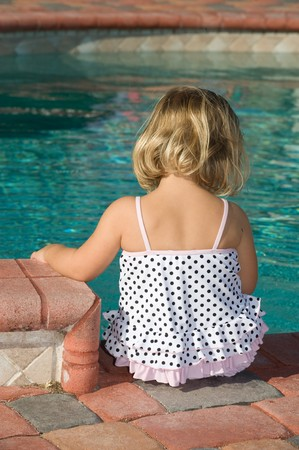 Little blond girl sitting by the pool in a polka dot swimsuit