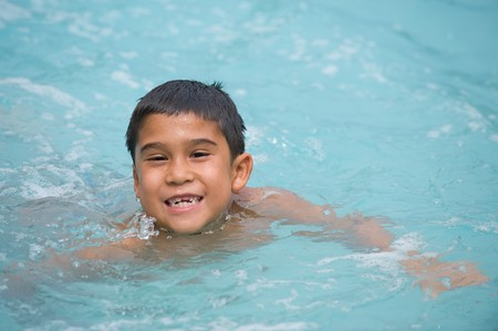 tread: Adorable young brunette boy swimming and smiling in the pool