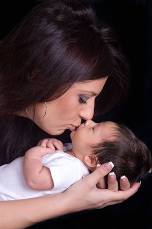 cradling: Beautiful mother kissing her newborn baby boy