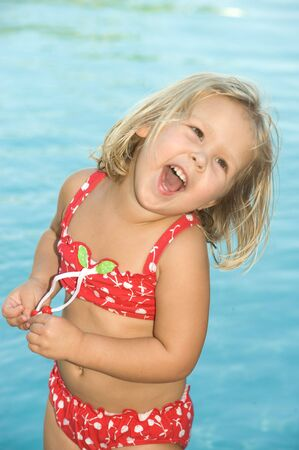 Adorable little blond girl in red swimsuit photo