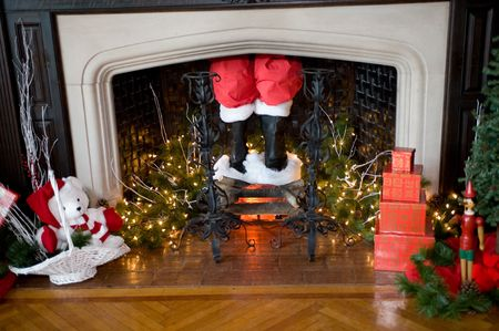 Santas pants and boots coming down the chimney with Christmas decorations around