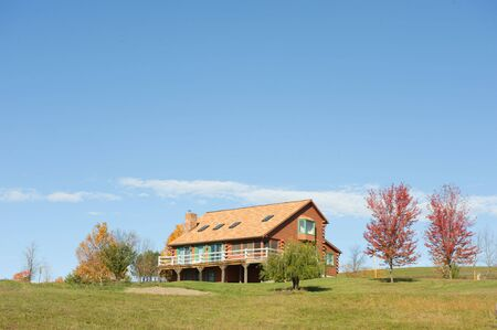 changing colors: Beautiful log cabin surrounded by trees with leaves changing colors