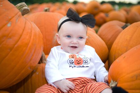Adorable baby in pumpkin patch smiling Stock Photo - 5362940