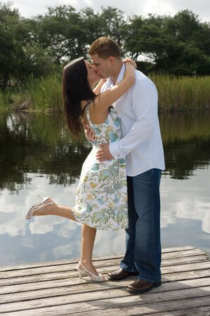 Couple kissing at the park by the lake Stock Photo