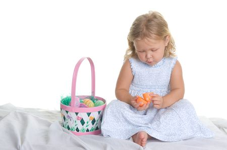 Adorable little blond girl in the studio with Easter eggs and basket