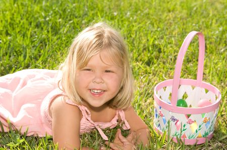 Adorable little blond girl with Easter basket smiling
