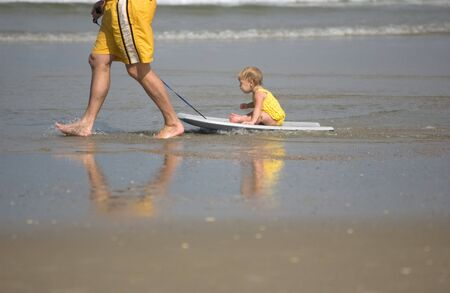 Father pulling little girl at the beach