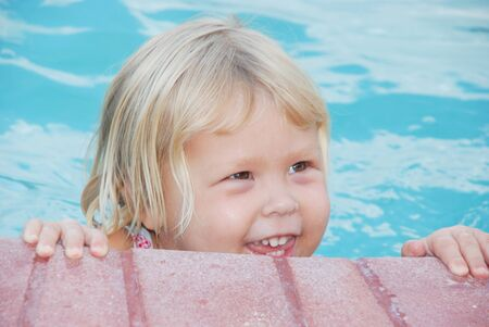Adorable little blond girl smiling in the pool