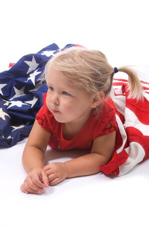 Adorable little blond girl with American flag in the studio