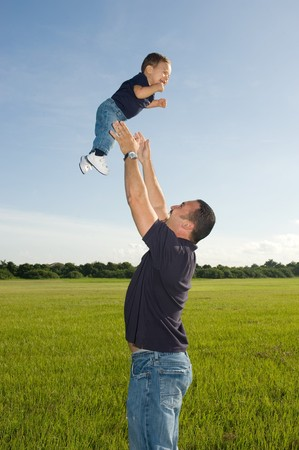 Father throwing son outdoors at the park