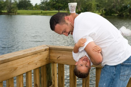 Father holding son upside down playing outdoors