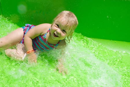 Adorable little blond girl smiling on a waterslide