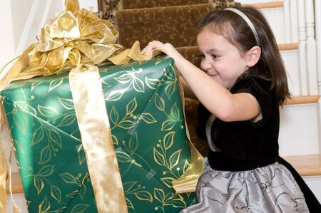 Adorable young brunette girl with a Christmas gift