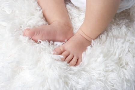 Baby feet on a white carpet