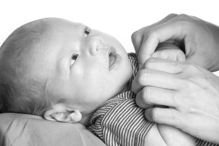 Beautiful baby boy holding mom s hands
