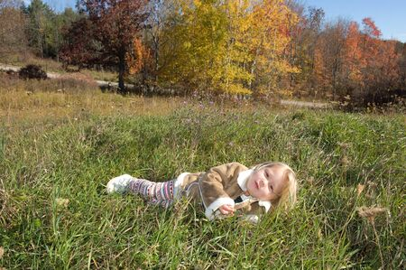 Adorable little blond girl in the fall