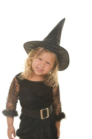 Adorable little blond girl smiling wearing a witch costume