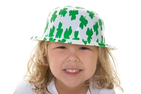Adorable little blond girl smiling wearing a shamrock hat