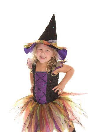 Beautiful little girl smiling in her witch costume on a white background
