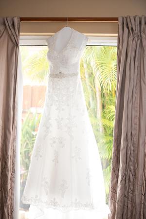 Beautiful wedding dress hung by a sliding glass door