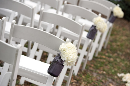 Beautiful flowers on chairs for wedding ceremony