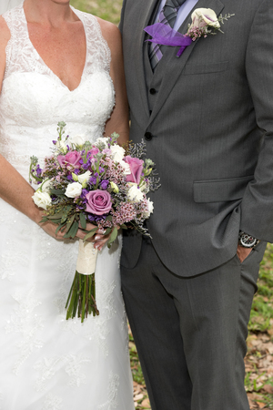 Close up image of bride and groom with bouquet