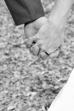 Black and white image of couple holding hands outdoors